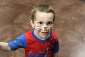 Child has face painted like a cat