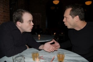 Writer and editor meet in restaurant. Both look passionate about what they're saying.