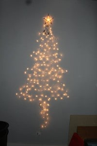Make a Christmas tree on the wall with just a strand or two of lights and whatever ornaments you have on hand.