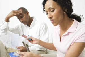 Couple going over bills, considering closing credit card accounts