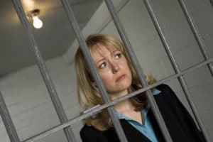 Editors cannot review books they edit, and doing so can cause problems. Image of female professional behind bars.