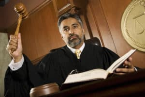Court judge with raised gavel reading list of words that indicate judgment