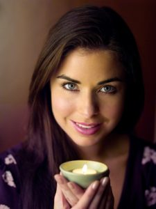 Using scented candles for focus is simple and pleasant, as this woman holding a vanilla candle shows.