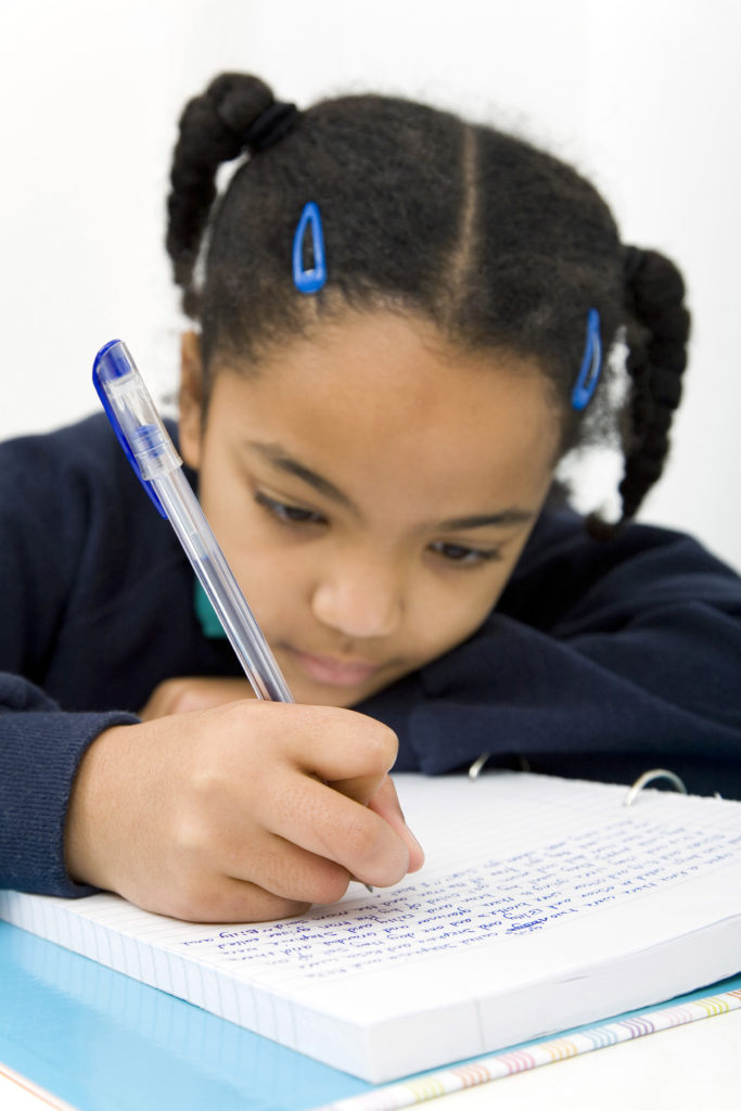 This child writing in a notebook will need affordable editing for child authors.